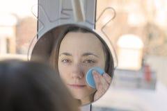 Una mujer que se admira en el espejo La mujer hermosa delante del espejo compone ella misma Imagenes de archivo