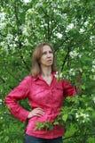 Una mujer que se coloca cerca del flor de la manzana Fotografía de archivo