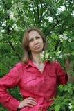 Una mujer que se coloca cerca del flor de la manzana Fotos de archivo