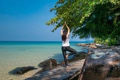 Una mujer que se coloca en una pierna mientras que practica yoga en el puente de madera sobre el mar durante vacaciones de verano imagenes de archivo