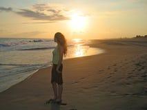Una mujer que se coloca en una playa Imagen de archivo libre de regalías
