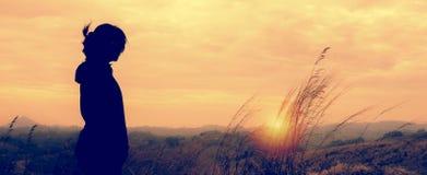 Una mujer que se coloca solamente en escena de la puesta del sol Fotografía de archivo