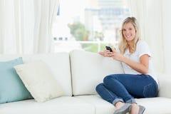 Una mujer que se sienta de lado en el sofá como ella utiliza su teléfono y Imagen de archivo libre de regalías