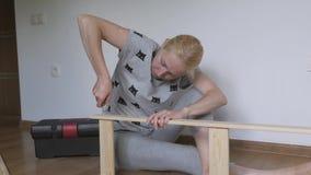 Una mujer que se sienta en el piso recoge los muebles de madera en el cuarto, tuerce los tornillos con un destornillador metrajes