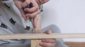 Una mujer que se sienta en el piso recoge los muebles de madera en el cuarto, tuerce los tornillos con un destornillador almacen de video