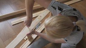 Una mujer que se sienta en el piso recoge los muebles de madera en el cuarto, tuerce los tornillos con un destornillador almacen de metraje de vídeo