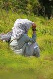 Una mujer que se sienta en el prado con las corrientes fuertes Imagenes de archivo