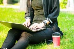 Una mujer que se sienta en la hierba mientras que usa el ordenador portátil con una taza de café roja Imagen de archivo libre de regalías