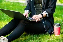 Una mujer que se sienta en la hierba mientras que usa el ordenador portátil con una taza de café roja Fotos de archivo libres de regalías