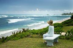 Una mujer que se sienta en un banco que pasa por alto el mar Imagen de archivo libre de regalías