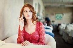 Una mujer que se sienta en un café con el teléfono celular Fotos de archivo libres de regalías