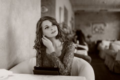 Una mujer que se sienta en un café con la tableta Fotos de archivo