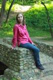 Una mujer que se sienta en un parapeto de piedra del puente Imagenes de archivo
