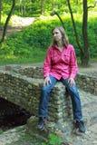 Una mujer que se sienta en un parapeto de piedra del puente Fotografía de archivo