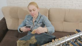 Una mujer que se sienta en un sofá examina y fotografía, usando un smartphone, una colección de ropa del dril de algodón que cuel metrajes