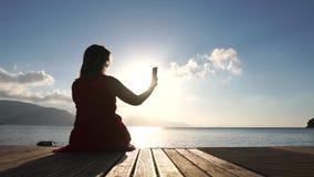 Una mujer que se sienta por el mar, tomando imágenes de una visión en la salida del sol, cámara lenta almacen de video