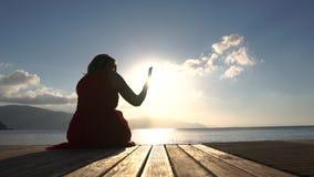 Una mujer que se sienta por el mar, tomando imágenes de una visión en la salida del sol en la cámara lenta almacen de metraje de vídeo