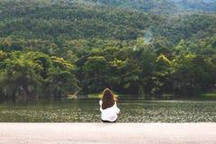 Una mujer que se sienta solamente por el lago que mira las montañas con la naturaleza nublada y verde fotos de archivo