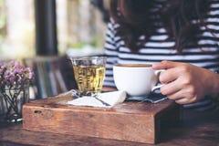 Una mujer que sienta y que sostiene una taza de café caliente y de un vidrio de té en la tabla de madera del vintage Imagen de archivo