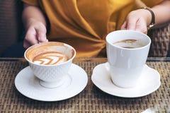 Una mujer que sostiene dos tazas del café con leche en café Imagen de archivo