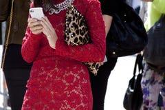 Una mujer que sostiene el vestido rojo del cordón del smartphone que lleva Fotografía de archivo