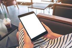 Una mujer que sostiene la PC negra de la tableta con la pantalla blanca en blanco mientras que se sienta en café imagenes de archivo
