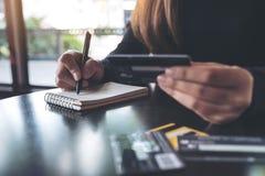 Una mujer que sostiene una tarjeta de crédito mientras que anota en el cuaderno en la tabla foto de archivo