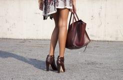 Una mujer que sostiene un bolso del diseñador y que lleva botines Foto de archivo libre de regalías