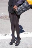 Una mujer que sostiene un bolso del diseñador y que lleva los tacones altos Imagen de archivo libre de regalías