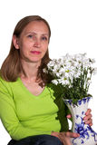 Una mujer que sostiene un florero con las flores aislado Fotos de archivo libres de regalías