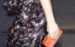 Una mujer que sostiene un monedero anaranjado del embrague Imagenes de archivo