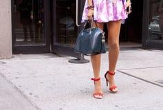 Una mujer que sostiene un monedero azul y que lleva los zapatos anaranjados Fotos de archivo libres de regalías