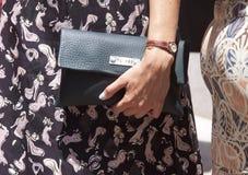 Una mujer que sostiene un monedero del embrague del diseñador Imágenes de archivo libres de regalías