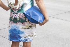 Una mujer que sostiene un monedero del embrague del diseñador y que lleva los tacones altos Fotografía de archivo