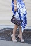Una mujer que sostiene un monedero del embrague del diseñador y que lleva los tacones altos Foto de archivo libre de regalías