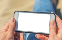 Una mujer que sostiene un tel?fono m?vil blanco con una pantalla en blanco imagen de archivo libre de regalías