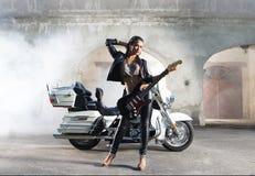 Una mujer que sostiene una guitarra y que presenta cerca de una bici Foto de archivo