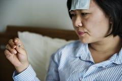 Una mujer que sufre de fiebre foto de archivo