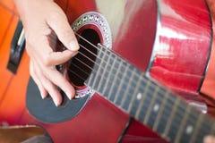 Una mujer que toca la guitarra Imagen de archivo libre de regalías