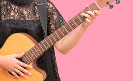 Una mujer que toca la guitarra acústica por el acorde C Fotografía de archivo libre de regalías