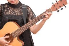 Una mujer que toca la guitarra acústica por el acorde C en el CCB blanco aislado Foto de archivo libre de regalías