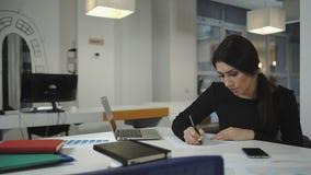 Una mujer que trabaja en el ordenador, tomando notas sobre una hoja, se arruga y los tiros almacen de metraje de vídeo