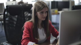 Una mujer que trabaja en la oficina en su ordenador metrajes