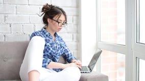 Una mujer que usa el ratón y el teclado al whie de Internet que practica surf se sienta en casa almacen de video