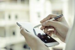 Una mujer que usa la tableta con la pluma de la aguja imágenes de archivo libres de regalías