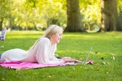 Una mujer que usa la tarjeta de crédito que hace compras en línea con un ordenador portátil en el p Imágenes de archivo libres de regalías