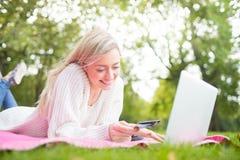 Una mujer que usa la tarjeta de crédito que hace compras en línea con un ordenador portátil en el p Imagen de archivo