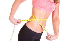Una mujer que usa una cinta métrica de medir su tamaño de la cintura Imagen de archivo libre de regalías
