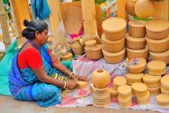 Una mujer que vende artículos del bambú y del bastón en ella parada Imagenes de archivo