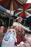 Una mujer que vende las muñecas de la moda en el mercado de Chatuchak, Bangkok Imagen de archivo libre de regalías
